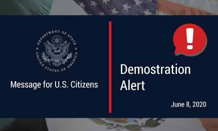 """The photo reads """"Message for U.S. Citizens"""", """"Demostration Alert, June 8, 2020"""". The photo has the logo, a speech bubble with an exclamation point, and the American and Mexican flags as the background."""