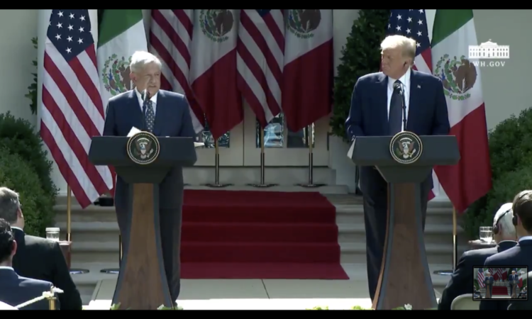 President Lopez Obrador and President Trump each stand behind their own podium on an outdoor stage. Behind them are the American and Mexican flags.