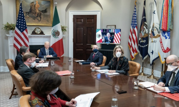 The picture shows a smiling President Biden seated at the head of a long wooden table in a conference room. He is seated with other officials who are wearing masks and looking at papers.