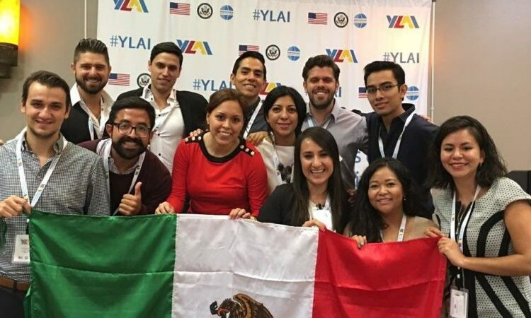 A group of youth holding the flag of Mexico