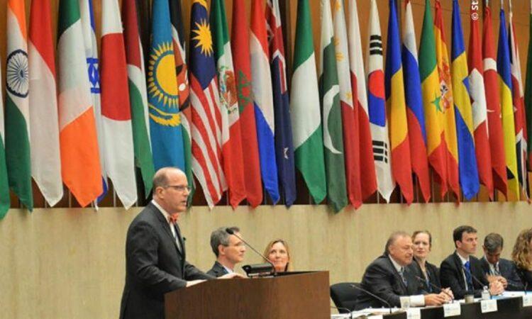 Man giving speech behind a podium next to other representatives