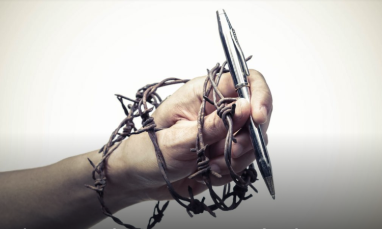 hand wrapped in barbed wire that is holding a pen