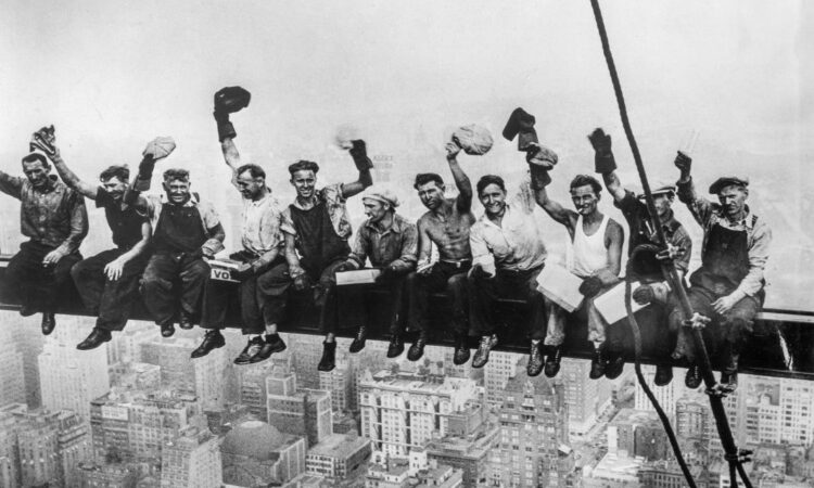 black and white photo of people posing on a beam