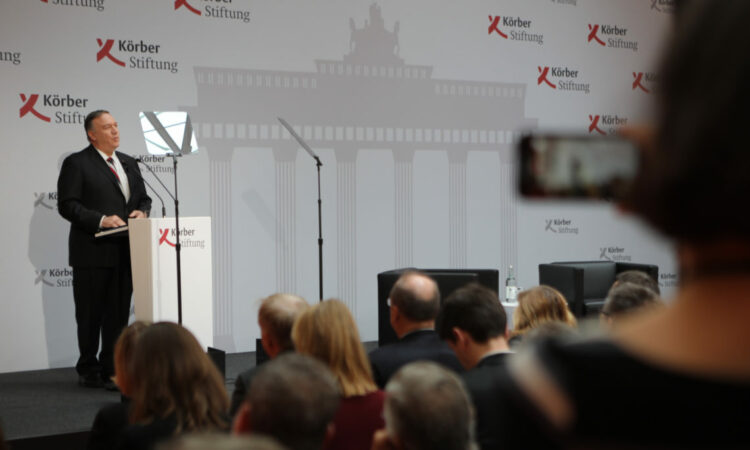 person standing behind a podium, giving a speech to an audience