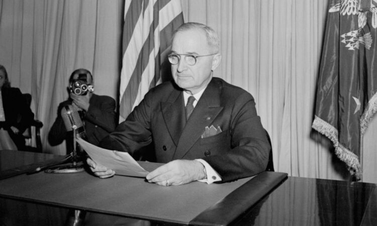 A man sits at desk with papers in hand.