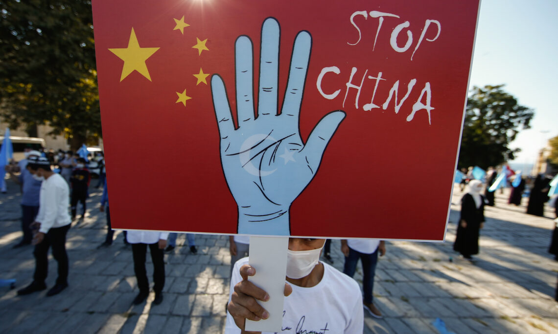 A protester from the Uighur community living in Turkey, holds an anti-China placard during a protest in Istanbul, Thursday, Oct. 1, 2020, against what they allege is oppression by the Chinese government to Muslim Uighurs in far-western Xinjiang province. China's government has been accused of human rights abuses against Uighurs and other predominantly Muslim minorities in the region. (AP Photo/Emrah Gurel)