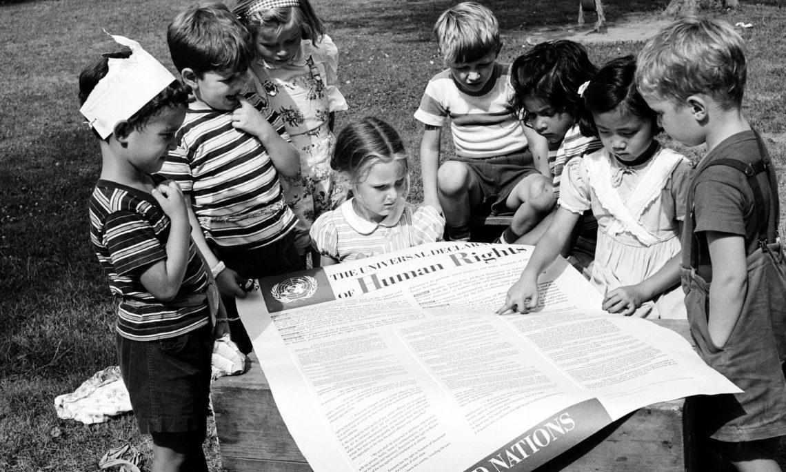 A groupie of children surrounding an article.