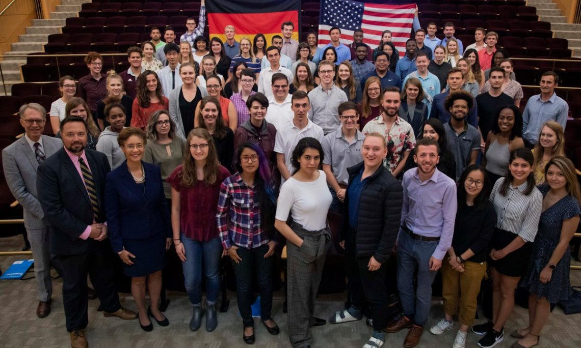 group of people standing in front of country flags