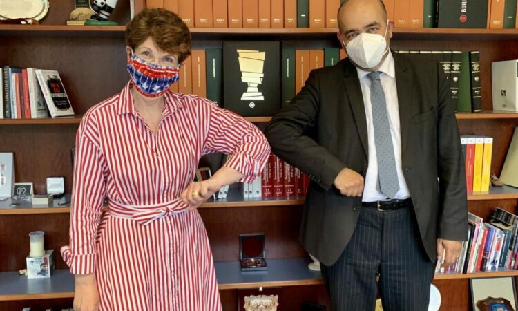 Woman and Man standing next to each other wearing face masks and touching elbows.