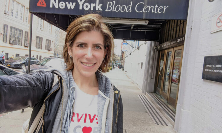 Woman smiling in front of blood center.