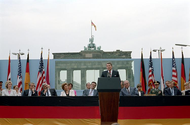 President Reagan speaking at lectern with Brandenburg Gate behind him