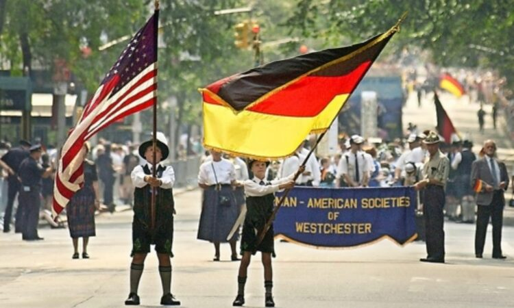Fahnenträger schwenken Flaggen der USA, Deutschlands