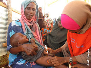 A mother holds her child for vaccination at a Somali refugee camp, where the risk of contagion can be higher than normal.