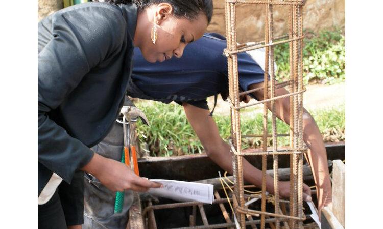Saba Bisrat reading from paper in front of building model (Courtesy of Saba Bisrat)