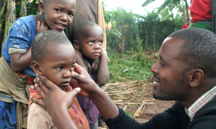 Man checking eyes of children to assess health (Echoing Green NYC/Flickr)