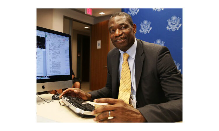 Dikembe Mutombo seated behind computer on table (State Dept.)