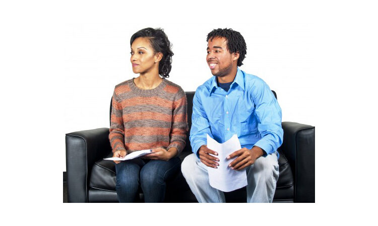 Smiling man and woman sitting on couch with resumes (Shutterstock)