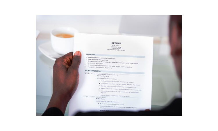 """Hand holding piece of paper titled """"Resume"""" (Shutterstock)"""
