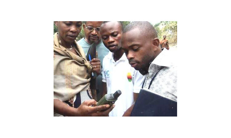 Person holding mobile phone as three others look on (USAID)