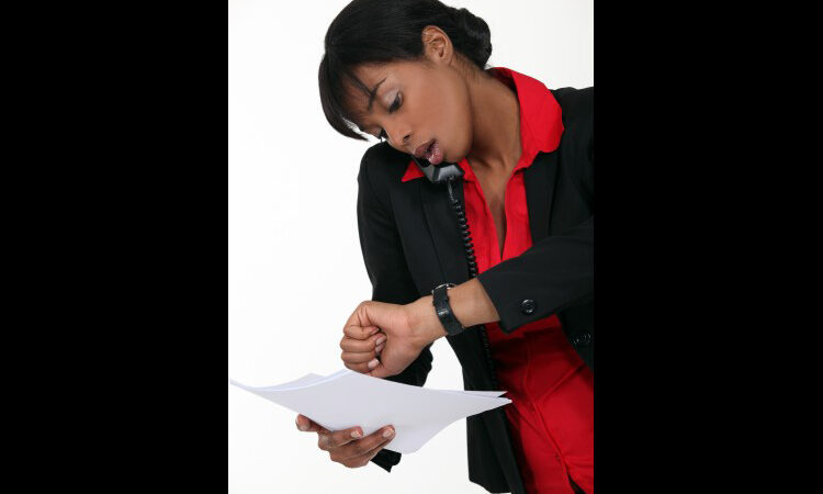 Alt: Woman talking on phone, holding papers and looking at watch on wrist (Shutterstock)