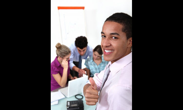 Man giving thumbs-up with three people working in background (Shutterstock)