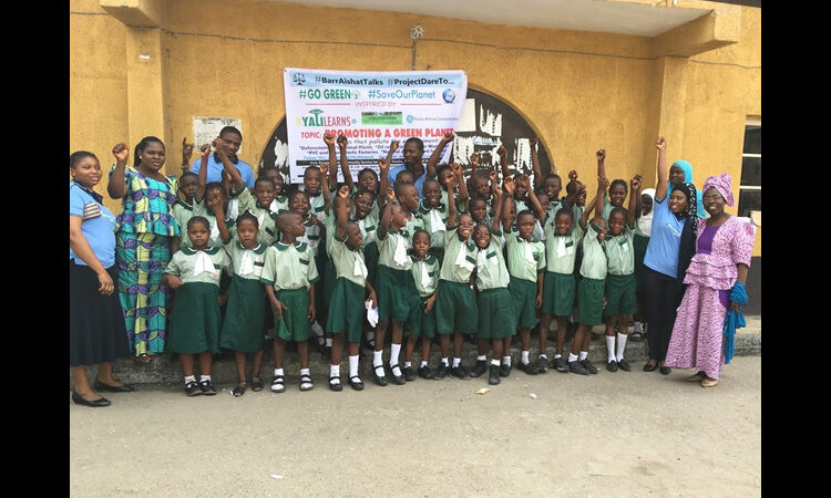Schoolchildren cheer and hold up a banner (Courtesy Aishat Hussain-Agberemi)
