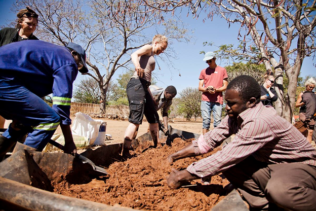 Men and women workers shoveling compost material (Courtesy of Greenpop)