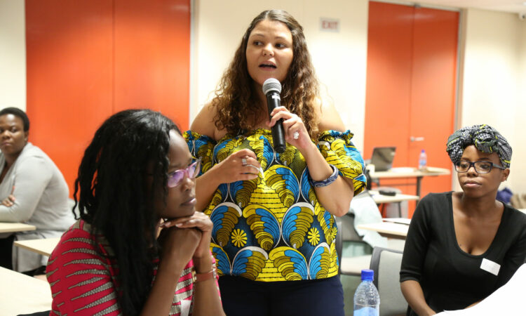 Lizette Feris speaking into a microphone in front of group (Courtesy photo)