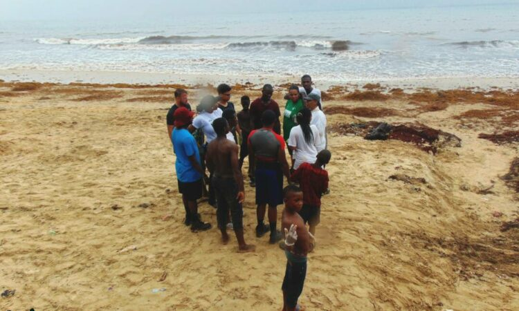 Group of people cleaning a beach in Freetown, Sierra Leone (Courtesy of James Metzger)