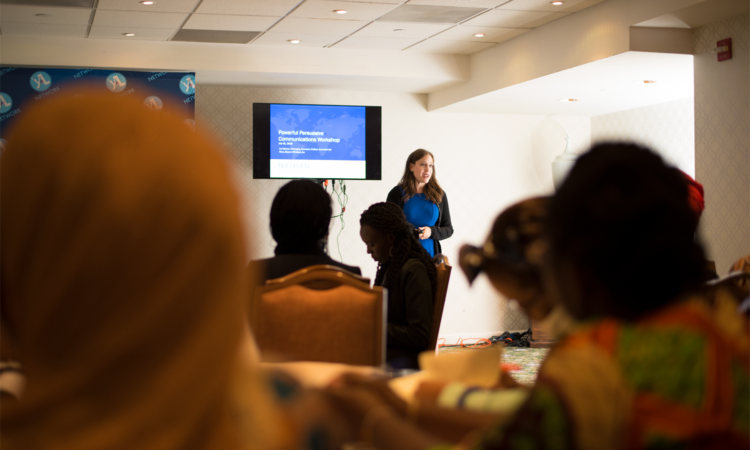 A woman gives a presentation entitled Powerful Persuasive Communication Workshop