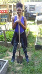 Tshinde Matos holding a shovel
