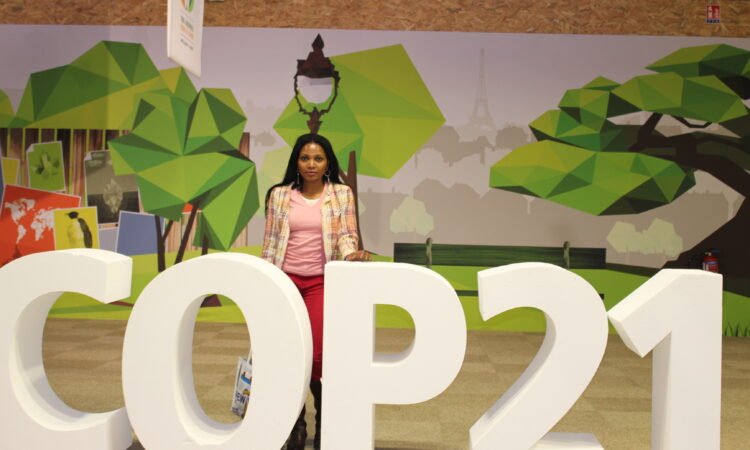 """Woman stands on a stage with large letters spelling """"COP21."""" (Photo courtesy Peace Sasha Musonge.)"""