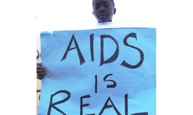 """Boy holding poster reading """"AIDS is real"""" (Peace Corps)"""