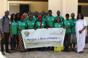 """Group of people standing, holding a sign reading """"Projet <<Eco-citoyen>>"""
