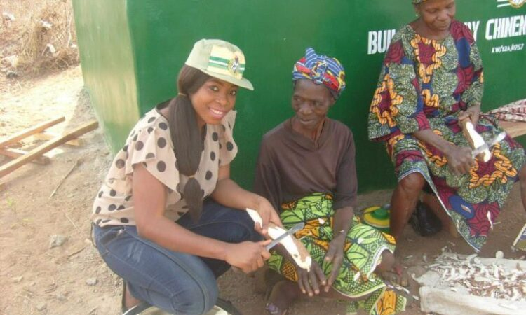 Glory and two farmers at her cassava factory in 2015