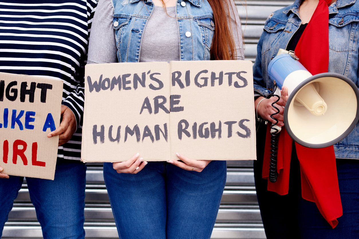 """Cropped shot of an unrecognizable woman holding up a poster that reads """"Women's rights are human rights"""" while protesting with other unrecognizable women in the city"""