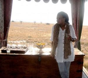 Woman leaning against table holding glass (Mavis Nduchwa)
