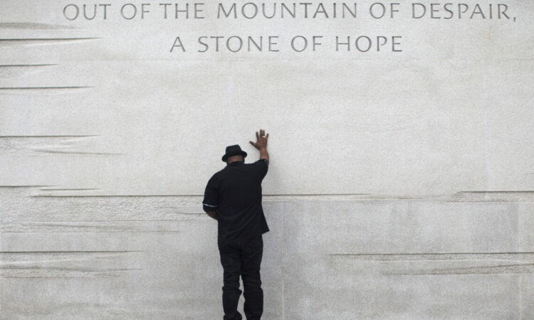 """A man puts his hand on a wall slab that reads: """"Out of the mountain of despair, a stone of hope."""""""