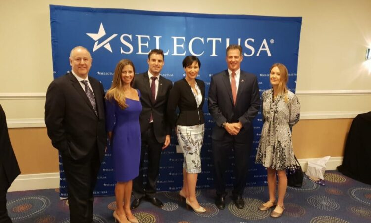 """A group of professionals stand in front of a banner that reads: """"SelectUSA."""""""