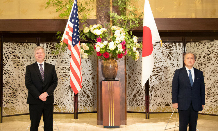 two people standing in front of the flags of the U.S. and Japan