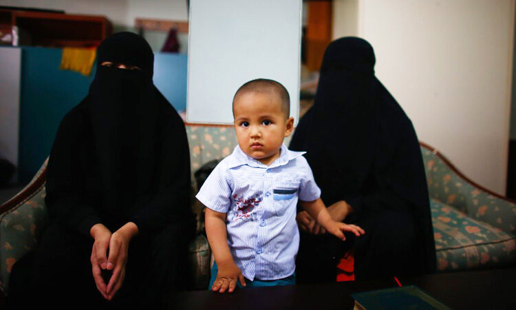 2 Muslim women with a toddler