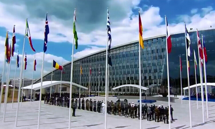 People in formation in front of NATO building