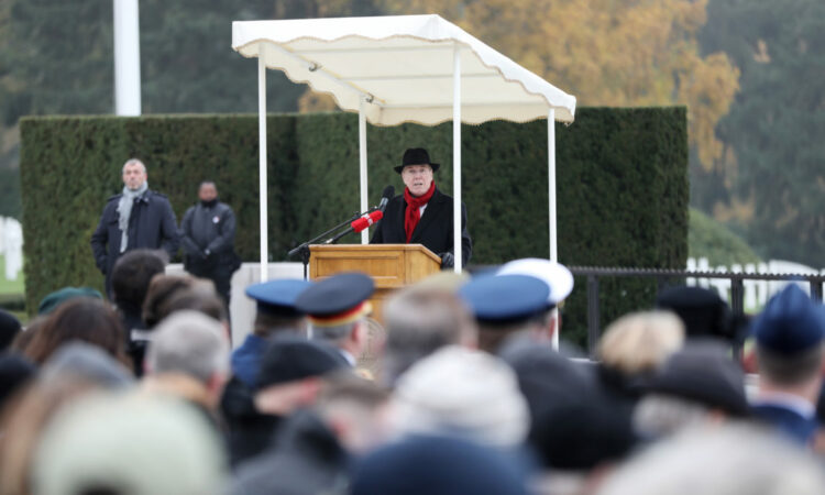 Ambassador Randy Evans speaks at the Veteran's Day ceremony on a podium under an awning in front of a crowd
