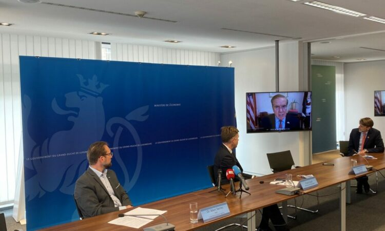 Watching Ambassador Randy Evans on the monitor from a table