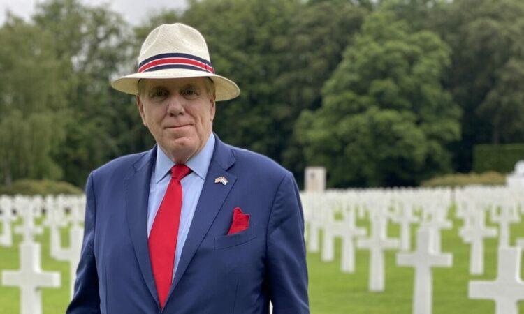 Ambassador Randy Evans poses in front of the memorial