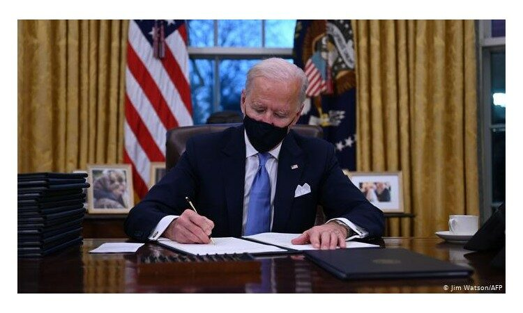 President Biden accepts the Paris Agreement on his desk in the oval office