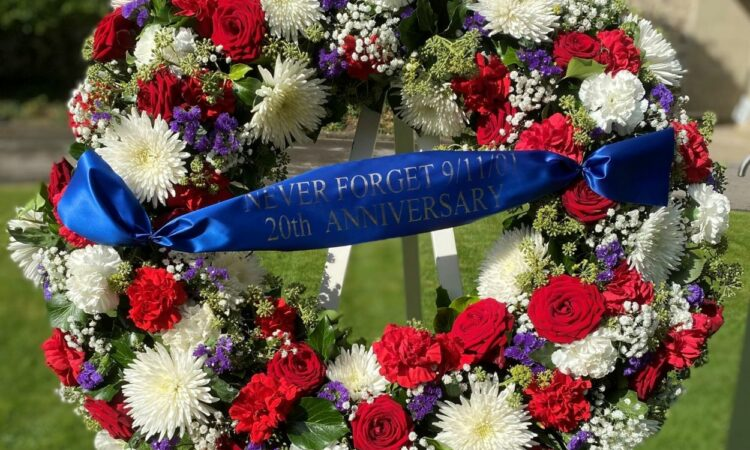 Red and White Flowered Wreath with Blue Ribbon