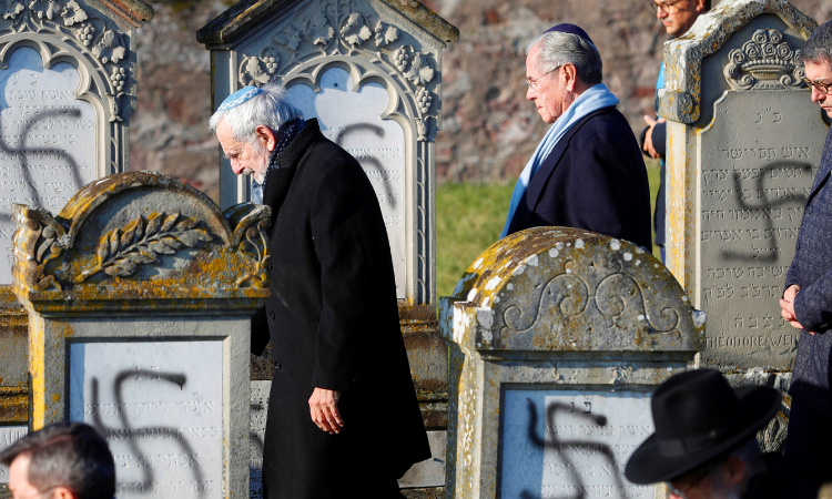 Members of the Jewish community walk amid vandalized tombs in the Jewish cemetery of Westhoffen, west of the city of Strasbourg, eastern France, Wednesday, Dec. 4, 2019. Regional authorities in eastern France say vandals have scrawled anti-Semitic inscriptions, including swastikas spray-painted in b
