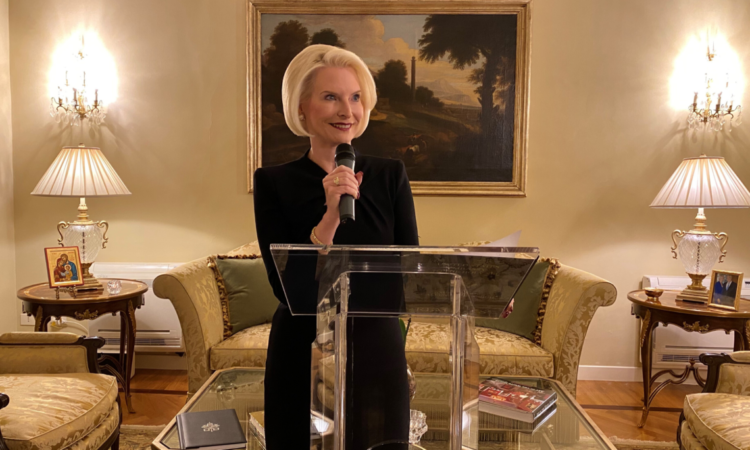 Ambassador Gingrich holding a microphone standing at a lectern giving a speech