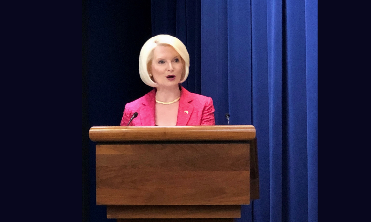 Ambassador Gingrich stands behind a wooden podium, giving a speech. A stage curtain can be seen behind her.